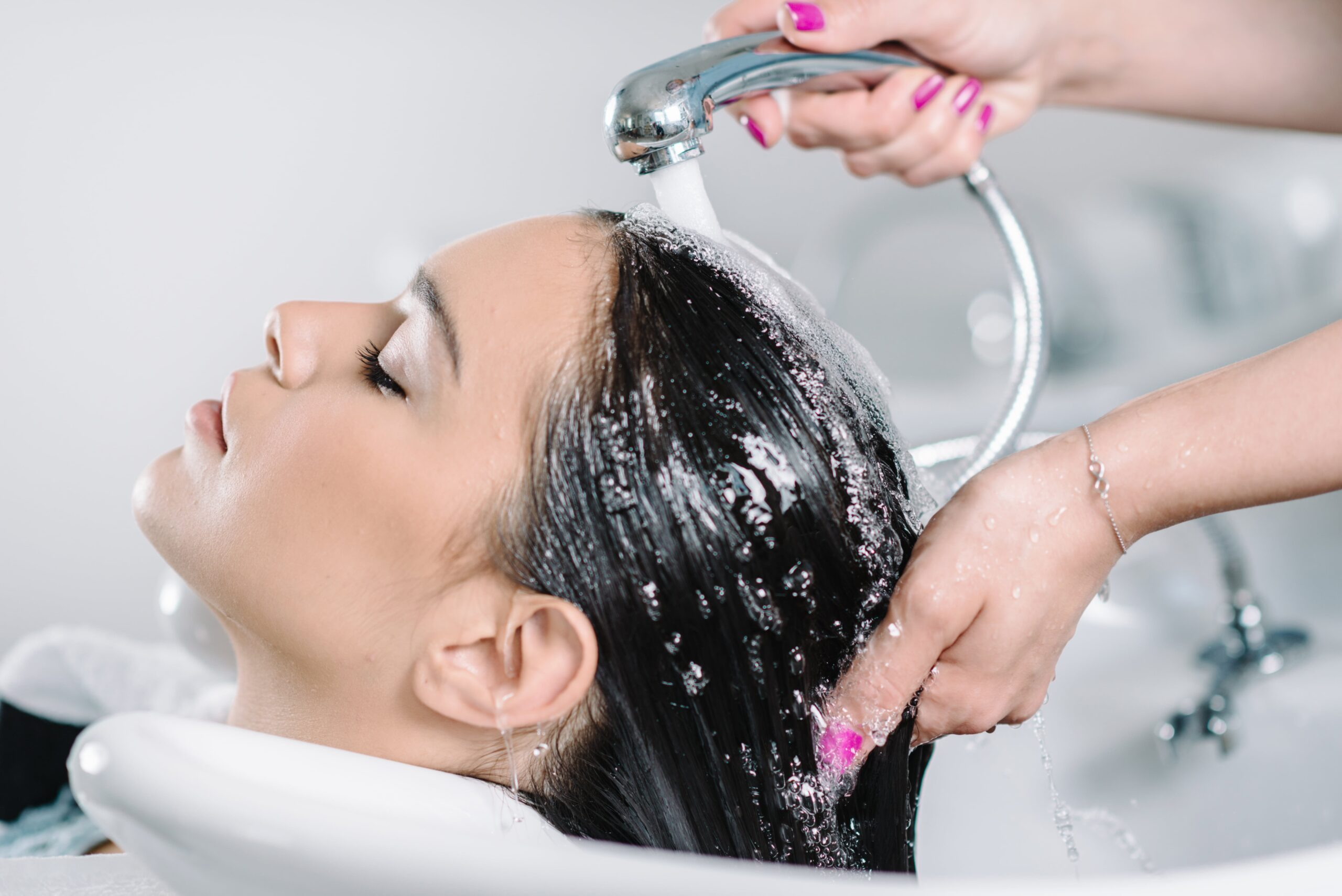 Glossary: Image of a woman having her hair washed in a salon.