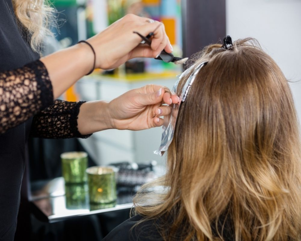 Highlights: Image of a hairdresser performing applying highlights on a client.