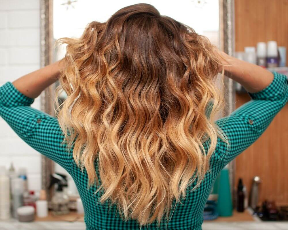 What is Ombre: Image of a woman with honey ombre hair.